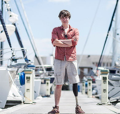 Man with prosthetic leg standing near boats